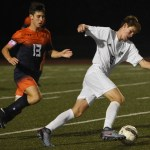 Junior Conor O'Toole dribbles the ball down the field away from his opponent. Photo by Ellen Swanson