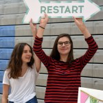"Juniors Annabelle Cook and Grace Padon hold up the sign that says ""Restart"" to market their share project to everyone in the gym and get them to sign up. Photo by Katherine Odell"