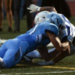 Junior Michael Perry tackles a Rockhurst player on the sideline. Photo by Lucy Morantz