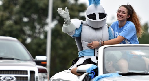 As one of the first cars to exit the East parking lot, senior Sophia Flannagan hugs the Lancer for a young parade viewer. Photo by Lucy Morantz