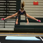 Sophomore Abby Gorman does a Shishanova (a straddle jump onto the floor) to warm up for her floor routine. Photo by Aislinn Menke