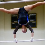 Sophomore Brooklyn Beck does a straddle to a handstand on the low bar in her routine. Photo by Aislinn Menke