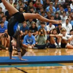 As the crowd cheers on the girls gymnastics team while they do their routine, sophomore Abby Gorman does a front handspring. Photo by Aislinn Menke