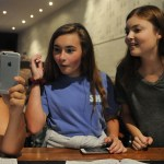 Seniors Grace Chisholm, Isabelle Cunningham, and Savanna Worthington laugh and smile while looking at a funny picture. Photo by Izzy Zanone