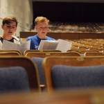 Juniors Henry Morgan and Jackson Engel sit and practice their music while they wait to go on stage. Photo by Izzy Zanone