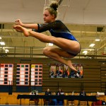 Junior Emily Eadens does a wolf jump during her floor routine. Photo by Aislinn Menke