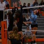 Sophomore Brigid Wentz jumps high to hit the ball over the net and scores a point. Photo by Aislinn Menke