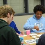 Freshman Julian Milton decorates his cookie while talking with friends. Photo by Ty Browning
