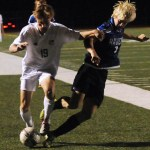 Junior Zach Bass pushes the opponent away to keep him from stealing the ball. Photo by Izzy Zanone