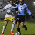 Junior Cooper Holmes fights for the ball against Olathe South forward. Photo by Carson Holtgraves