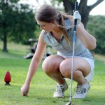 Junior Emily Fey sets up her tee so she can start at a new hole. Photo by Izzy Zanone