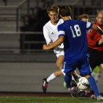 Junior forward Cooper Holmes collides with a Leavenworth defender while dribbling towards the goal. Photo by Lucy Morantz