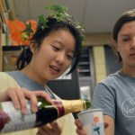 Sophomore Lily Turner pours sparking grape juice for Junior Nat Nitsch. Ancient Romans drank wine with every meal, so the juice was used as a substitute. Photo by Ally Griffith