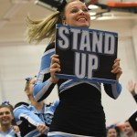 Senior Anna Mclelland leads the cheer squad onto the mat. Photo by Carson Holtgraves