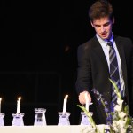 Senior Jonah Golder lights the last candle to represent the last of the five NHS pillars, character. Photo by Ellen Swanson