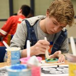 Using pictures for inspiration, sophomore Fischer Kirchhoff decorates a cookie. Photo by Grace Goldman