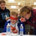 Junior Dane Erickson and sophomore Peter Kohring prepare junior Zane Meeks for the blindfold food tasting challenge. Photo by Grace Goldman
