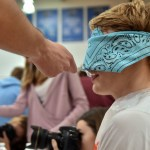 During the blind food testing game, senior Oscar Safferstein is fed by senior Reser Hall. Photo by Lucy Morantz