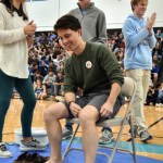 To finish the assembly, senior and student body president Denny Rice pulls his pants over his knees to prepare to get waxed. Photo by Lucy Morantz