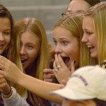 Juniors Catherine Ehrich, Hannah Goettsch, Meg Thoma, and Addie Von Drehle watch a video they recorded of a Mr. Cansas contestant's talent performance. Photo by Luke Hoffman