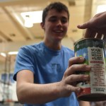 Running up the the junior bleacher's section, junior Will Thomas collects money to contribute for the can drive. Photo by Morgan Plunkett