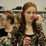 Sophomore Lucy Brock re-applies makeup before act two. Photo by Maddie Smiley