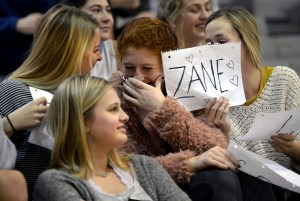 While watching the boy's scrimmage, junior Meredith Norden laughs with junior Gracie Kost, Addie Von Drehle and Sarah Grimm as they hold up posters to support the players. Photo by Ellie Thoma