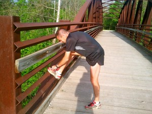 Houston Franks, the head cross country coach at Mississippi State University, takes a quick breather to tie his shoe during a trail jog. Light exercise such as jogging or hiking are perfect for active recovery days.
