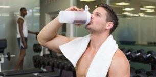 Shirtless bodybuilder drinking protein drink sitting on bench at the gym