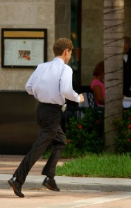 Businessman running across street
