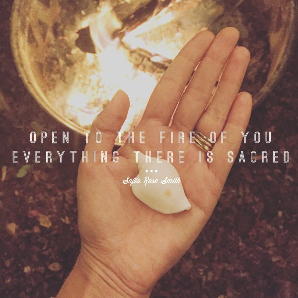 "A photo of a fire pit. A hand over the fire holds a white shell. Script on top of the image is ""Open to the Fire of You / Everything There is Sacred -Sofia Rose Smith"