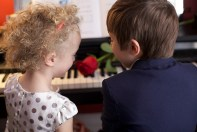 TWO CHILDREN AT THE PIANO WITH A ROSE—Photo by Karen Rodriguez