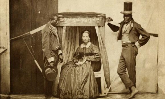 """Senhora na liteira (uma espécie de """"cadeira portátil"""") com dois escravos, Bahia, 1860 (Acervo Instituto Moreira Salles)"""
