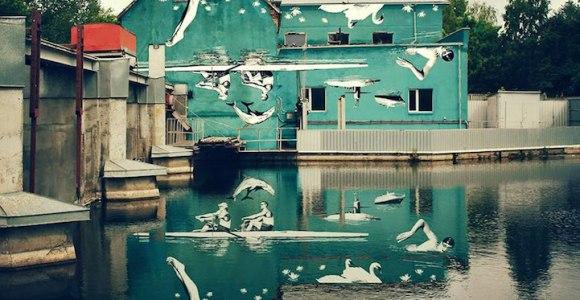 Artista pinta mural de ponta cabeça para ser visto no reflexo da água