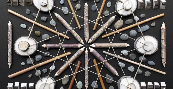 Artista organiza pedras e pedaços de madeira para criar mandalas