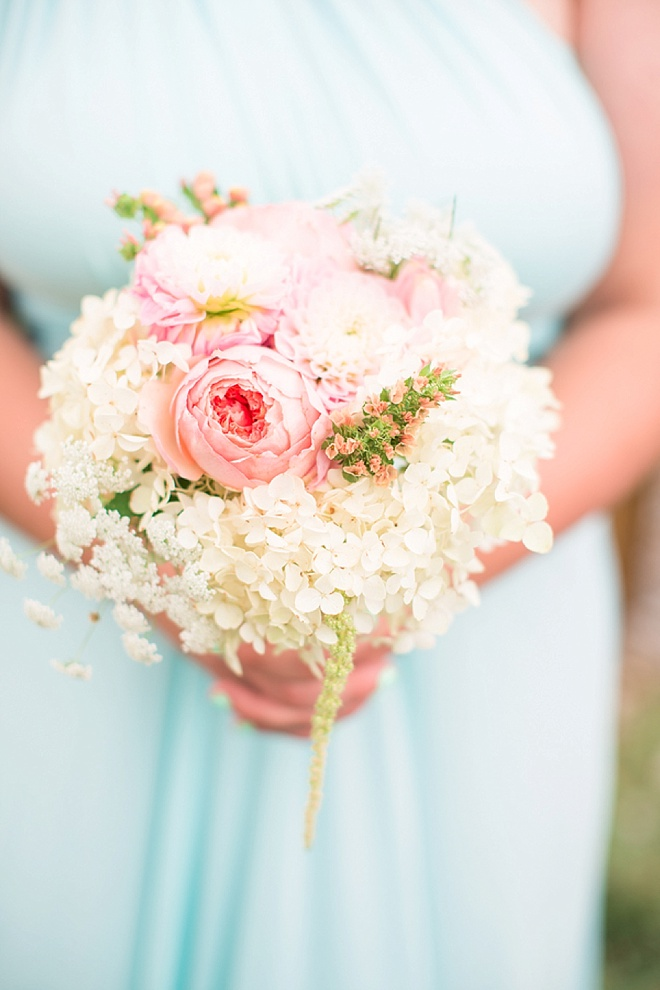 Bridesmaid holding gorgeous bouquet full of cabbage roses, hydrangea and amaranthus