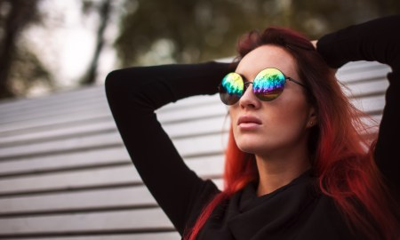 Sexual red hair woman in mirrored glasses in park
