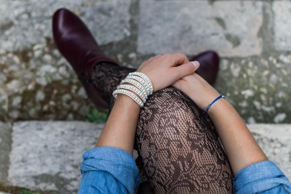Zoom sur le bracelet en perles Victoria Emerson et le collant résilles