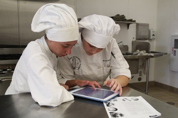 iPad technology assists seniors Tavia Parker and Cassadie Medall in the kitchen as they prep their dish. This is the third-year that Apple has presented this award based on usage of their products by students and staff.Photo Credit: Tamara Navarro
