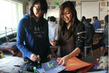 """Sophomores Maria Gamboa and Marissa Villarosa add glitter to their poster for their assigned element. """"This PBL has made me creative!"""" Villarosa said.  Photo Credit: Jen Chiang"""