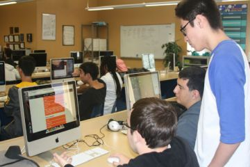 Web Design seniors Evan Schonhoff, Michael Shizuru and Javier Salazar review a site and code designed by a junior. They will be conducting the Hour of Code on Dec. 10.  Photo Credit: Alexis Drevetski