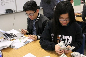 "Senior class treasurer Kelly Siu counts the money received for senior class shirts. The senior shirts will be distributed before winter break, along with revealing the approved senior song list. ""Seeing the shirts and knowing the song choices makes me excited for graduated,"" Siu said. Photo Credit: Mika Pagado"