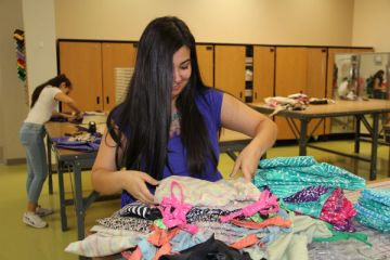 """Sophomore Mia Brewer sorts through the pile of hand-made shorts that will be sent to Africa in June. She has helped make six dresses in the past two months. """"Just the act of servicing Africa and realizing how one small person can help other people in such a big way is just so amazing,"""" Brewer said.  Photo Credit: Jen Chiang"""