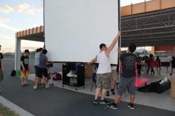 Students begin setting up the screen for this year's Movie Night. The event faced an unexpected halt when projection equipment lost power.