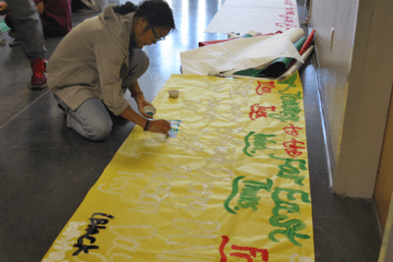 """Senior Vahina Li creates a poster detailing the upcoming spirit days. Each day was made final yesterday. """"Spirit Week serves as an outlet for most kids, including myself, to be creative and wear something out of the norm,"""" Li said.  Photo Credit: Brandon Hatch"""