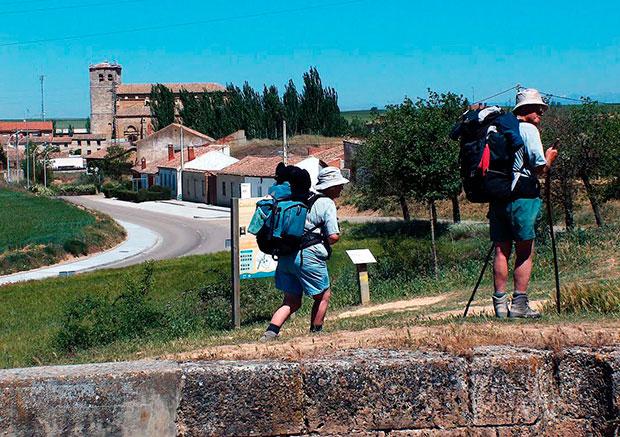 Peregrinos en el Camino de Santiago llegan a Frómista con la iglesia de Santa María al fondo