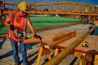 Carpenter's Apprentice, JoAnn, cutting plywood braces for concrete forms.