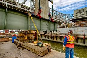 Mike Haycraft looks on as Todd Johnson and Charlie Draper attach rigging to the first Edge Girder for the Downtown Span of the Ohio River Bridges Project by Walsh Construction.