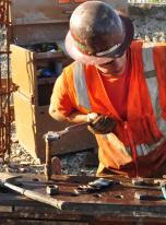 Carpenter Max Shaugnessey tightens bolts for a support beam.