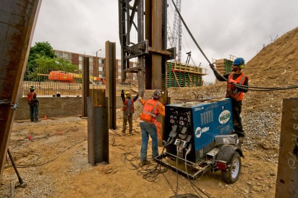 Pile driving crew placing a piling section for welding before driving further into the earth. #4